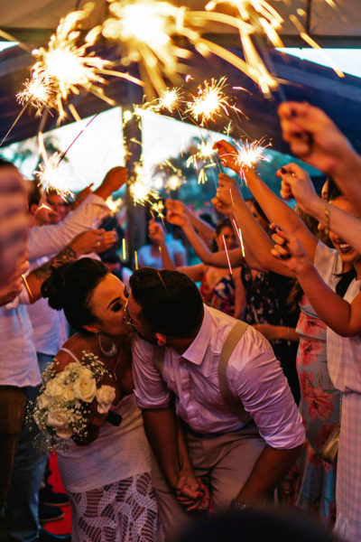 Photo of a Couple Kissing During Thie Wedding Exit Under Sparklers