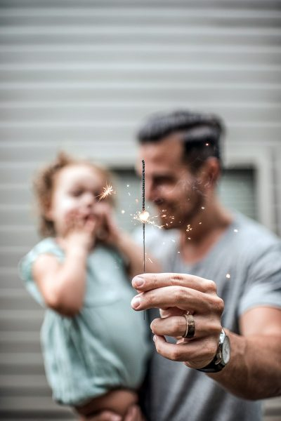 Image of a Father Holding His Daughter and a Sparkler at a Wedding