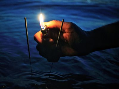 Image of a Person Lighting 2 Sparklers so they can Burn in the Water