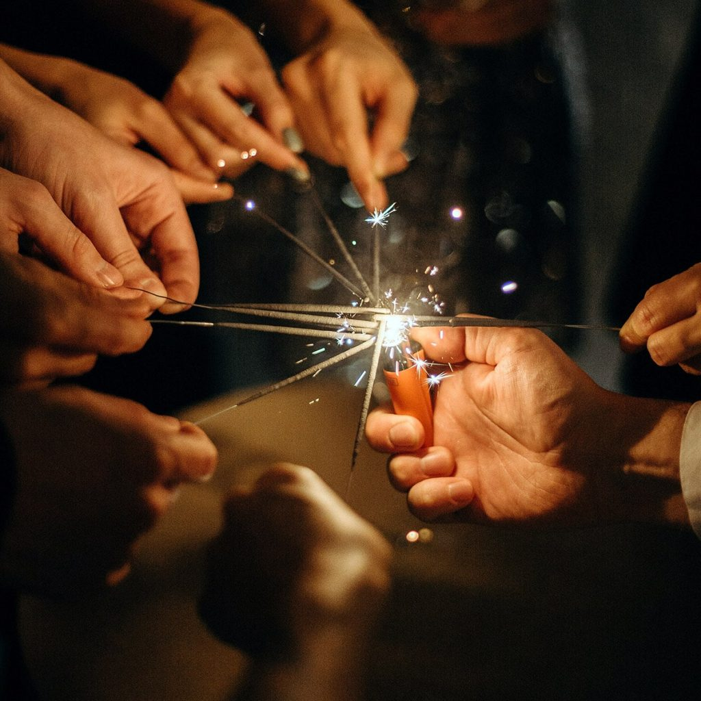 Image of People Lighting Multiple Sparklers at Once at a Wedding