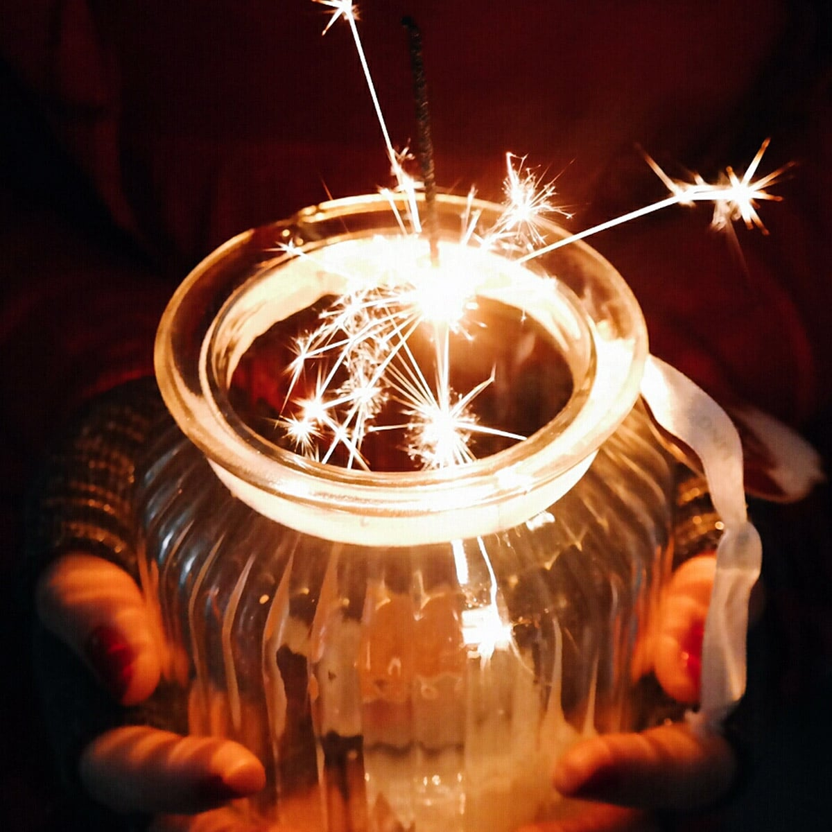 Image of a Bride Holding a Small Vase Full of Sparklers