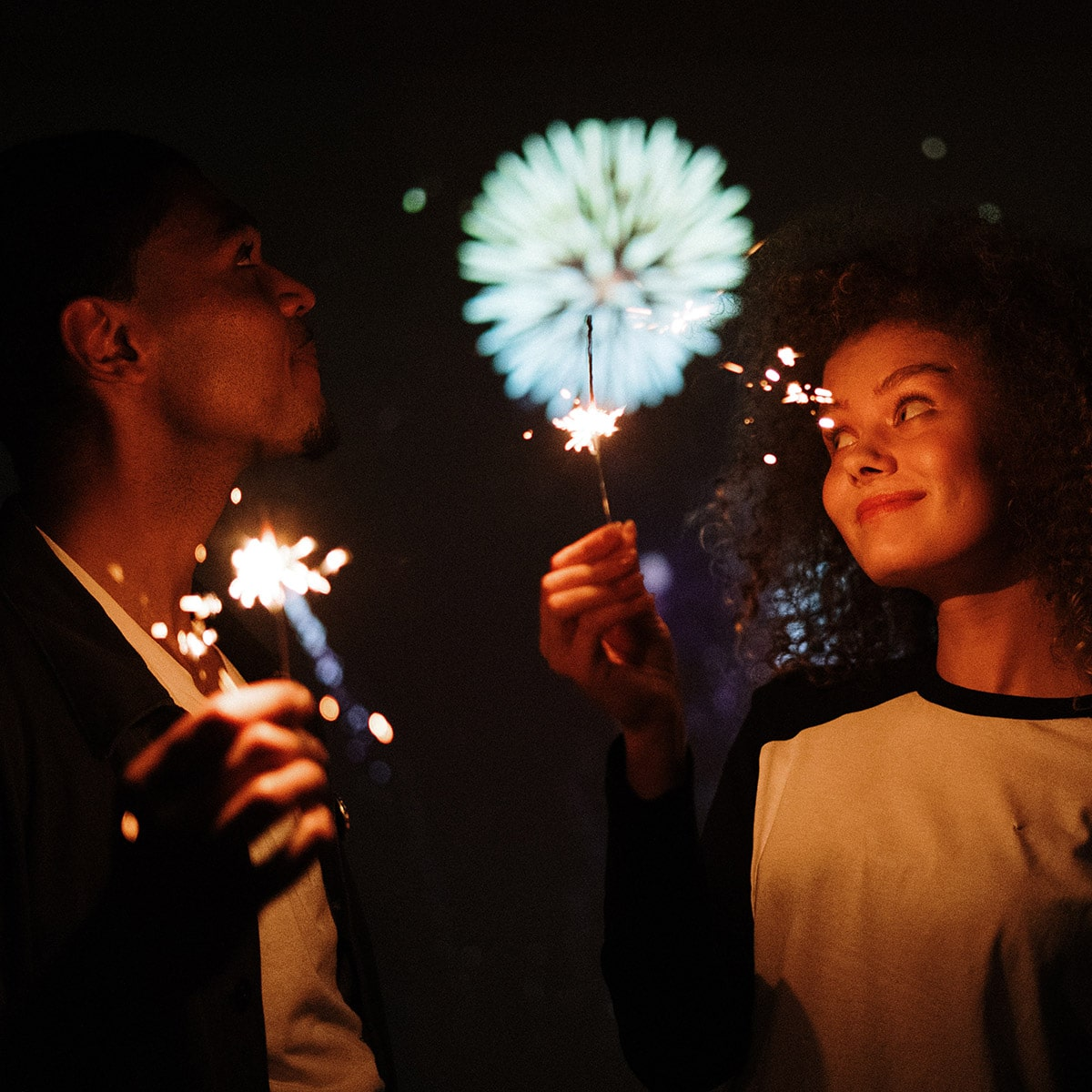 Image of 2 Teenagers Sharing a Sparkler While Watching the Fireworks
