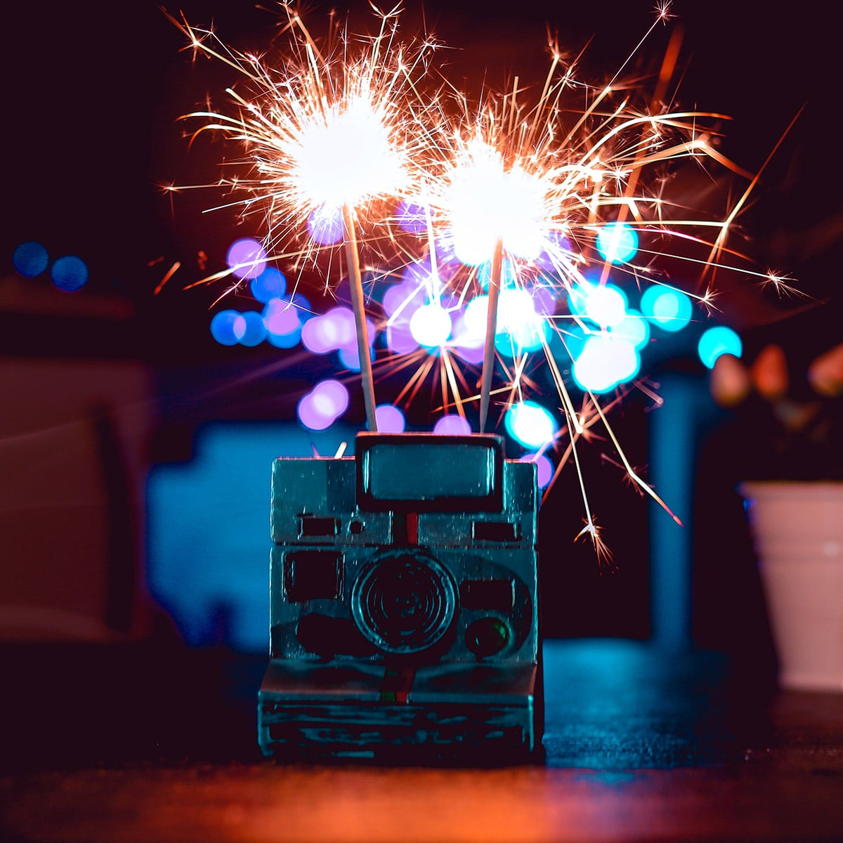 Image of a Couple Using Sparklers for Centerpieces Shaped Like Cameras