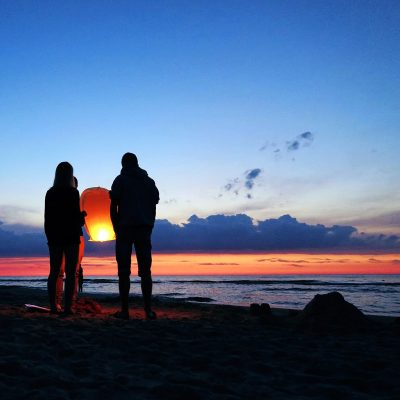 Image of People Releasing Sky Lanterns at a Beach Wedding