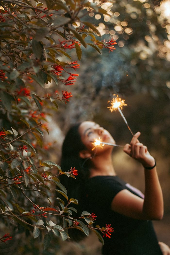 Image of Gril Using Sparklers Under the Trees