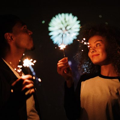 Image of Teenagers Using Sparklers During a Fireworks Show