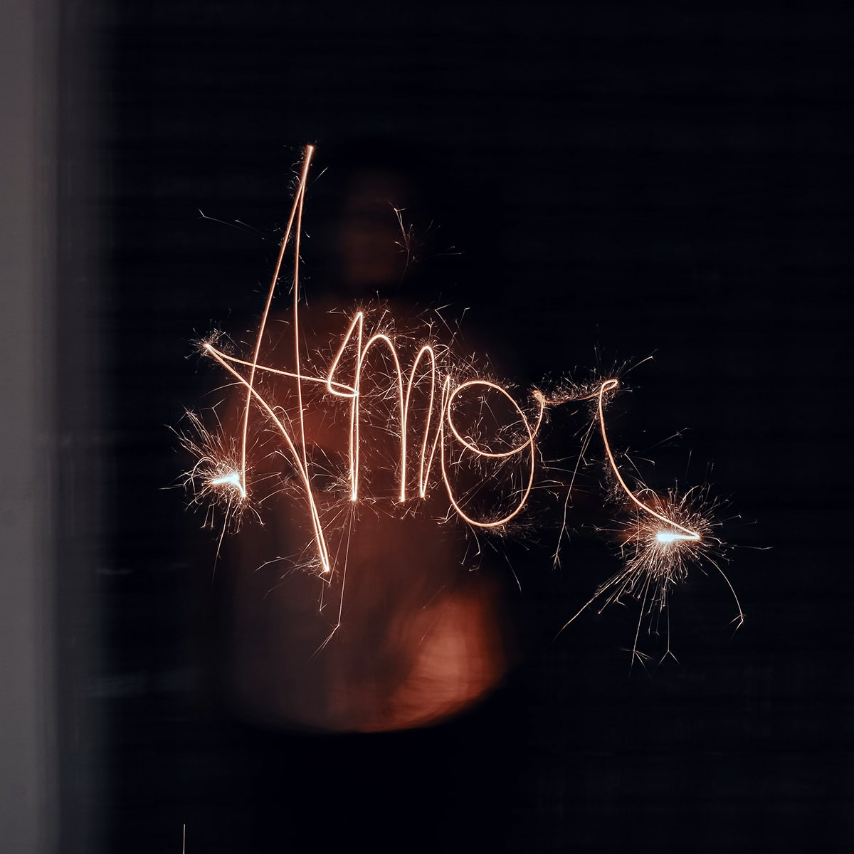 """Image of a Person Writing the Word """"AMOR"""" with Sparklers"""