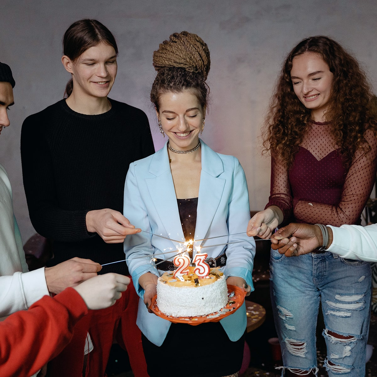 Image of People Lighting Sparklers with a Birthday Candle