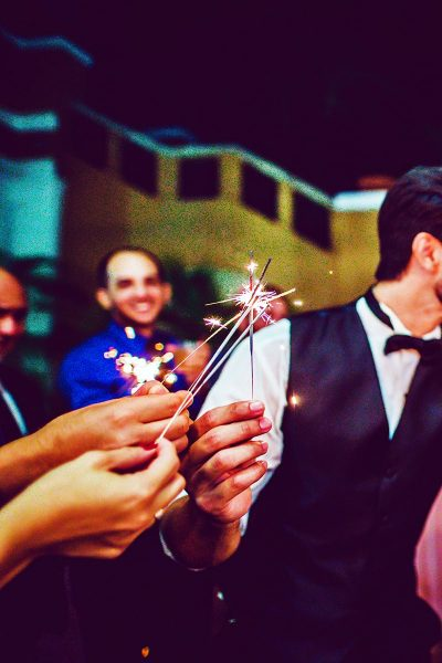 Image of Groom Lighting Sparklers With Another Wedding Sparkler